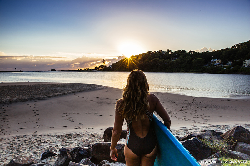 Girl walking along beach with paddleboard at sunrise