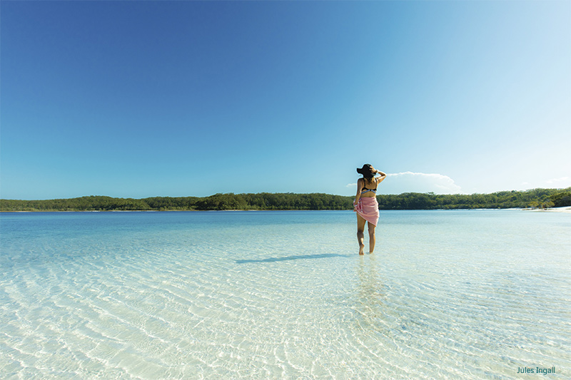 Girl standing in clear waters of Lake McKenzie credit Jules Ingall