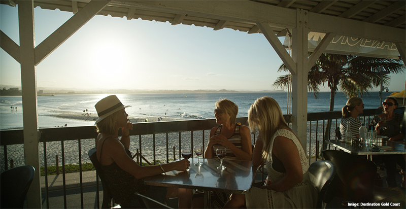 People sitting in a cafe overlooking the beach Destination Gold Coast
