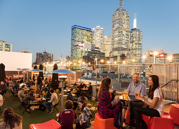 People enjoying a rooftop bar in Melbourne, Australia